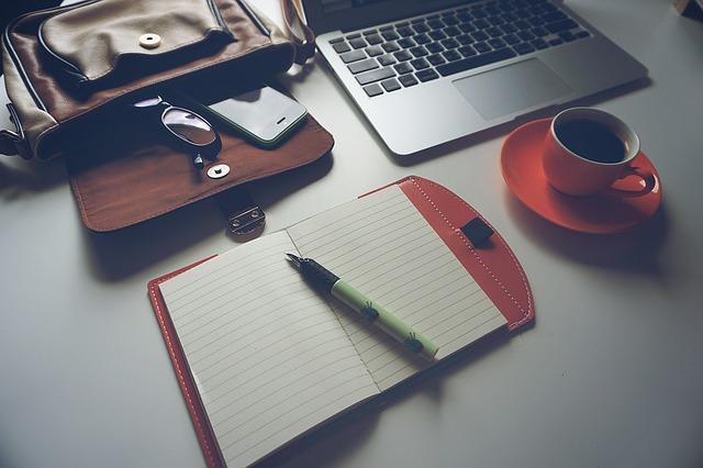 brýle, mobil, notebook, hrnek, sešit a tužka